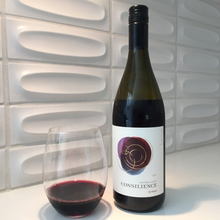 Bottle and glass of Consilience 2017 Syrah