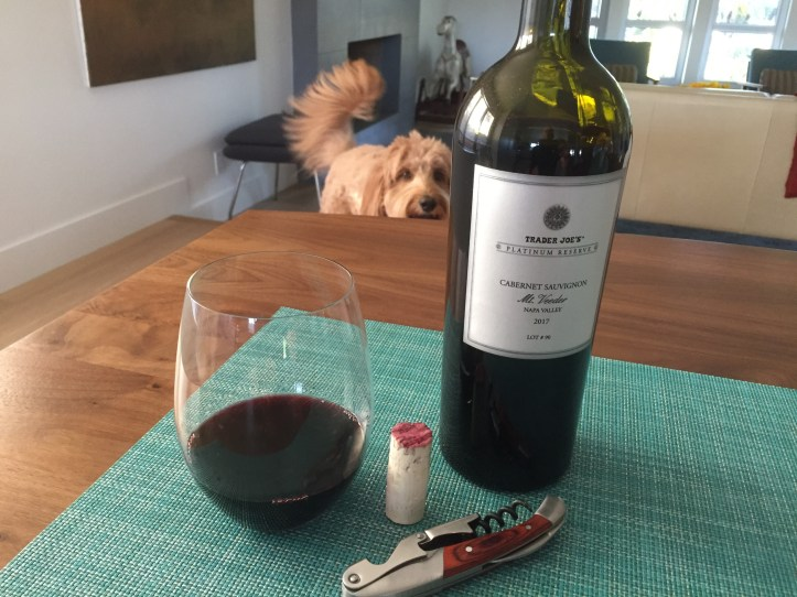 Glass and bottle of Trader Joe's 2017 Platinum Reserve Mt. Veeder Napa Valley Cabernet Sauvignon with a Labradoodle photobomer