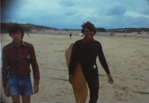 A Still image from a vintage home movie taken in the 1970s of a couple surfing in the uk
