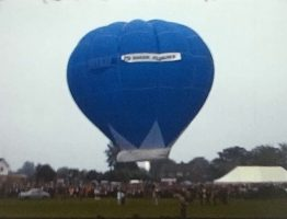 A still image from a vintage home movie showing a hot air balloon being launched