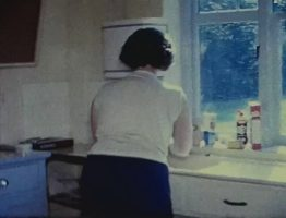 A still image from a vintage home movie of a typical family house of the 1950s