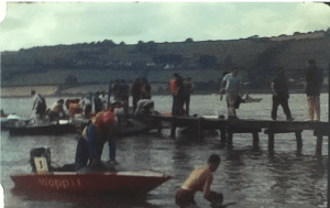 A still image from a vintage home movie which shows speed boats racing on a lake or waterway