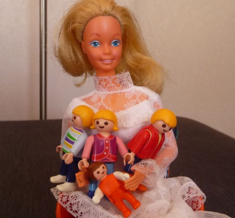 Barbie en robe de mariée qui a des enfants Playmobil sur les genoux
