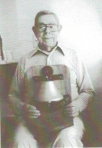 Red (now middle aged) proudly displays a replica of his ship's (USS Portland) bell.