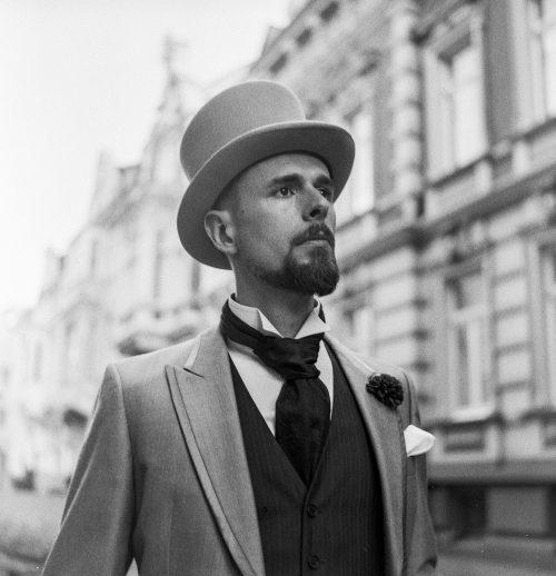 Analoge Schwarz/Weiß-Aufnahme von grauem Cut, Kläppchenkragen, Krawattenschal und Zylinder.