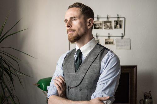 Hellblaues Hemd mit weißem Kragen, dunkelgrüne Krawatte aus Seidengrenadine und grau-karierte Weste mit Schalkragen