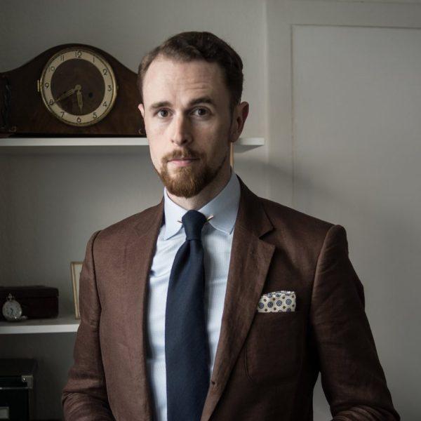 Fischgrat-Wollkrawatte auf Hemd aus feinem Hahnentritt. Einstecktuch mit Muster und braunes Jackett aus Leinen.