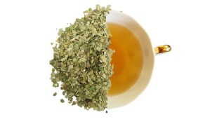 Brazilian green mate tea leaves over a cup of steeped tea