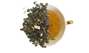 mango oolong loose leaf tea displayed over a brewed cup of tea