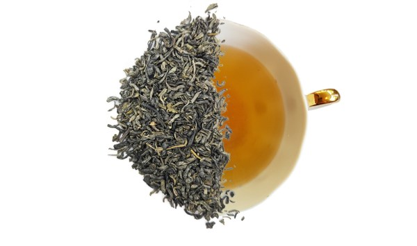 chunmee green tea leaves displayed over a brewed cup of tea