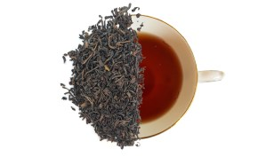 New England breakfast tea leaves displayed over a brewed cup of tea