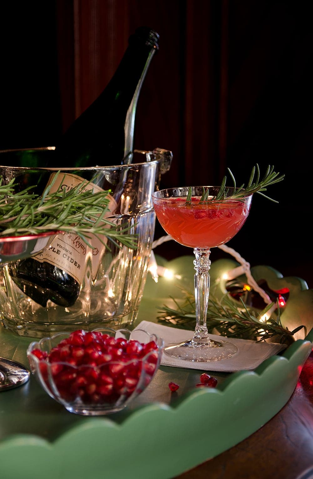 Saucy Santa Cider Cocktail tastes like Christmas! Bubbly hard cider, fresh pomegranate seeds and springs of rosemary come together to make a festive holiday drink. Let's toast to the season!   vintagekitty.com