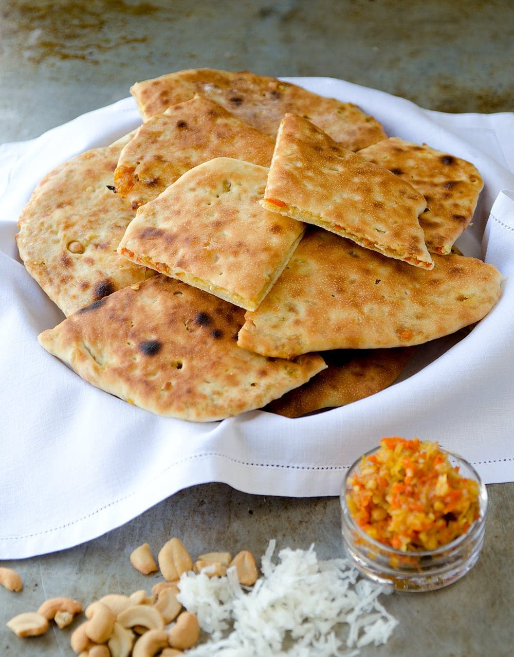 Naan with Candied Carrots, Cashews and Coconut is a unique addition to a Thanksgiving meal. Think beyond the standard rolls this holiday season. This naan recipe will surprise and delight guests with its sweet taste and tender crust. | vintagekitty.com