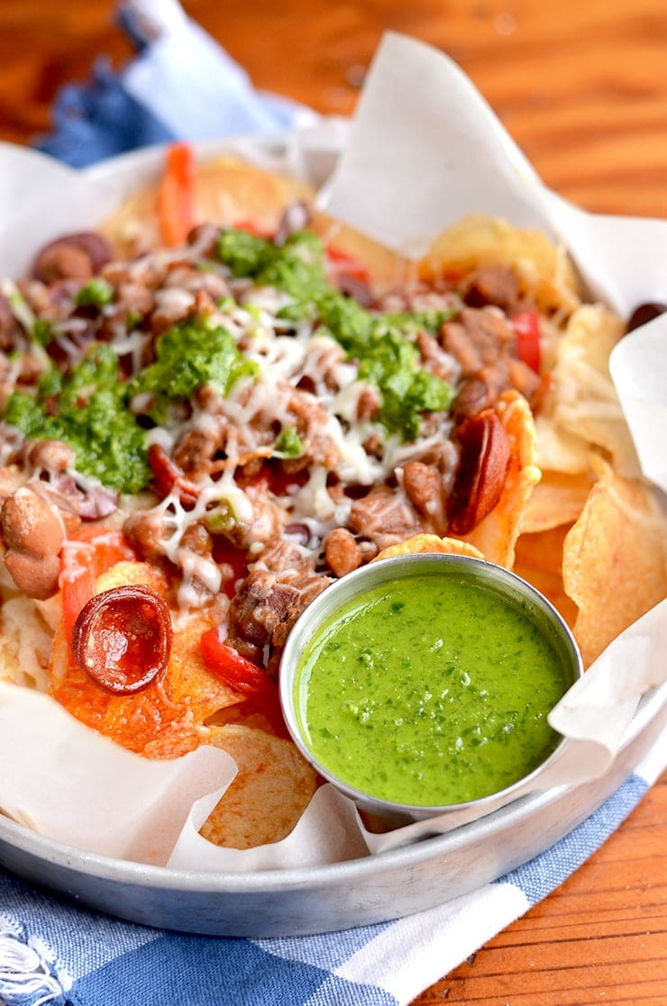 Homemade potato chips get loaded with savory ingredients in this Spanish Potato Nachos recipe. Far from ordinary, these nachos are topped with Manchego cheese, Chorizo sausage and served with a fresh, zesty Chimichurri.   vintagekitty.com