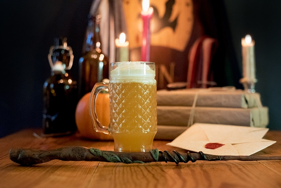 Butterbeer on a table with other Harry Potter props