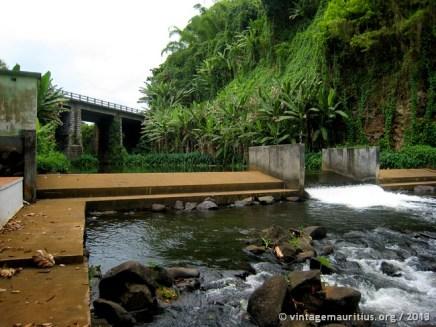 Small dam at the river bank, bridge at the back