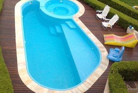 Construção de piscina arredondada, com hidromassagem e deck em madeira.