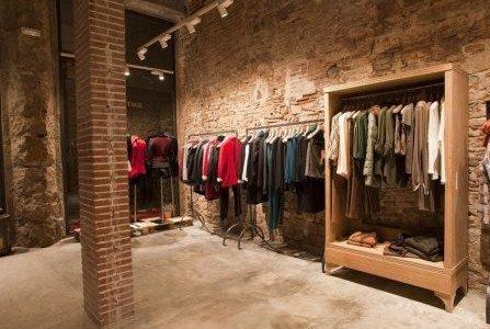 Remodelação de loja de roupa com parede em pedra à vista.