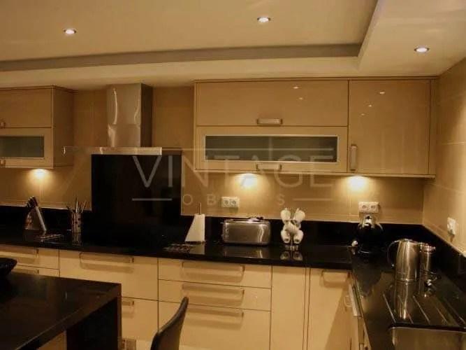 Remodelação de cozinha: Móveis lacados a branco e tampo em granito negro angola