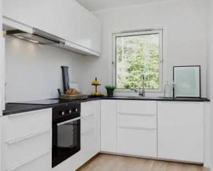 Remodelações de cozinhas com móveis lacados e tampo em granito negro a contrastar.