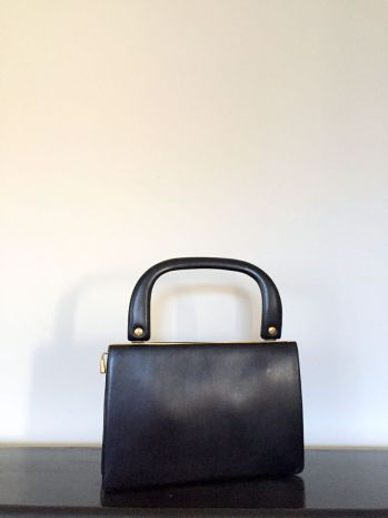 VINTAGE BLACK LEATHER HANDBAG WITH BRASS TRIM AND RED LINING
