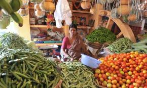 An Indian vendor waits for customers at a vegetable market in Hyderabad