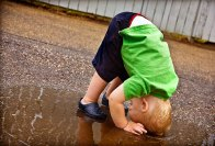 getty_rf_photo_of_boy_playing_in_rain_puddle