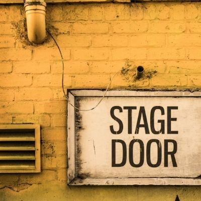 """yellow brick wall with a white sign that reads """"stage door"""""""