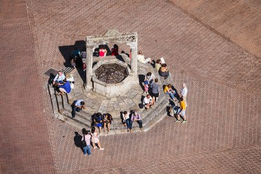 """Aerial view of people sitting around the medieval well in """"Piazza della Cisterna"""" in San Gimignano, Tuscany, Italy."""