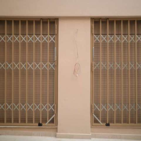 Retractable steel gate for a door