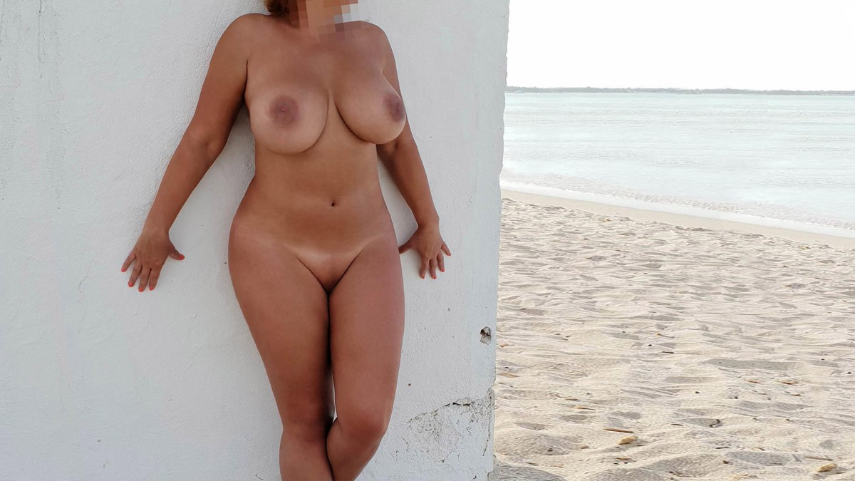 Sofia BBW VIP Escort standing on the beach with huge boobs in a wet T-shirt