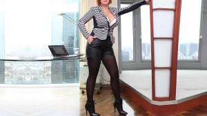 Sofia Elite escort BBW in sexy secretary look in shorts and nylons, with a large bust in a wide neckline