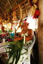Artisane à Fakarava, tresse une palme de cocotier pour en faire en chapeau. Woman artisan in Fakarava breading a coconut palm to make a hat.
