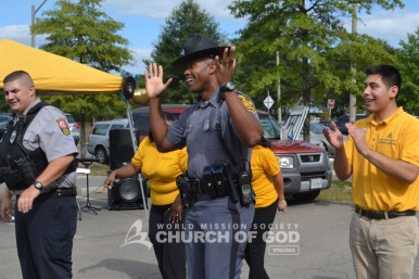 An officer throws his hands up in the air during the electric slide contest.