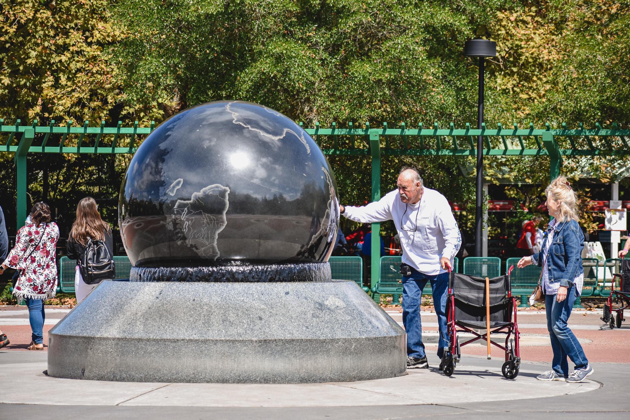 Older man touching a globe
