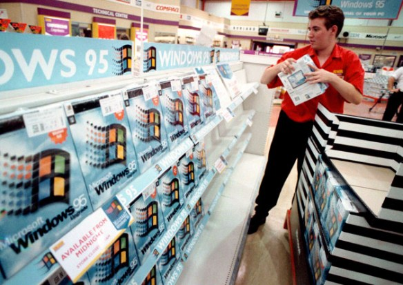 A worker packs the shelves of PC World, Croydon, with copies of the Microsoft Windows 95 upgrade computer package. The package will go on sale at midnight across the country.