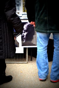 John Lennon's face peeks out from behind two pairs of legs at a vendor's booth near the memorial.