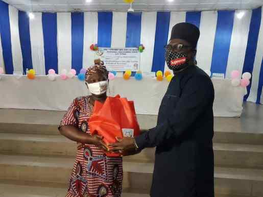 Francis Okoya, le Représentant du parrain de l'événement, le président Louis Gbèhounou Vlavonou remet ici un kit à une bénéficiaire