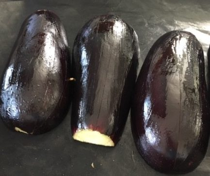 Place aubergines with flesh side down in a large greased non-stick tray. Lightly grease the skin of the aubergines.
