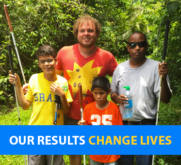 Photo: Brian Bushway stands with three students in Belize. Caption: Our Results Change Lives.