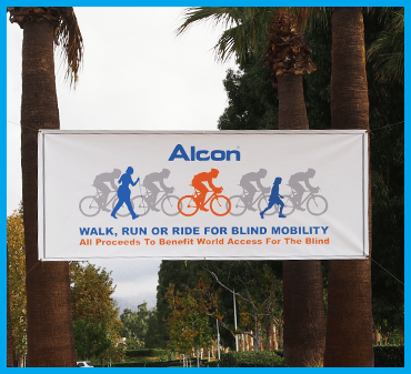 Image of outdoor banner tied between palm trees. Banner text reads Alcon Walk, Run or Ride for Blind Mobility. All proceedds to benefit World Access For The Blind. Banner images show cyclists, a child running and a woman walking with navigation canes.