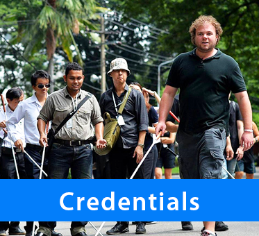 Photo: Brian Bushway leading a group of blind coach trainees along a street in Bangkok, Thailand. Caption: Credentials.