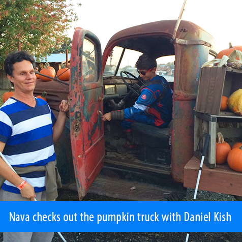 Nava checks out the pumpkin truck with Daniel Kish. Photo shows Daniel holding the driver's side door open of a vintage flatbed truck with Nava in the driver's seat rolling the window down.