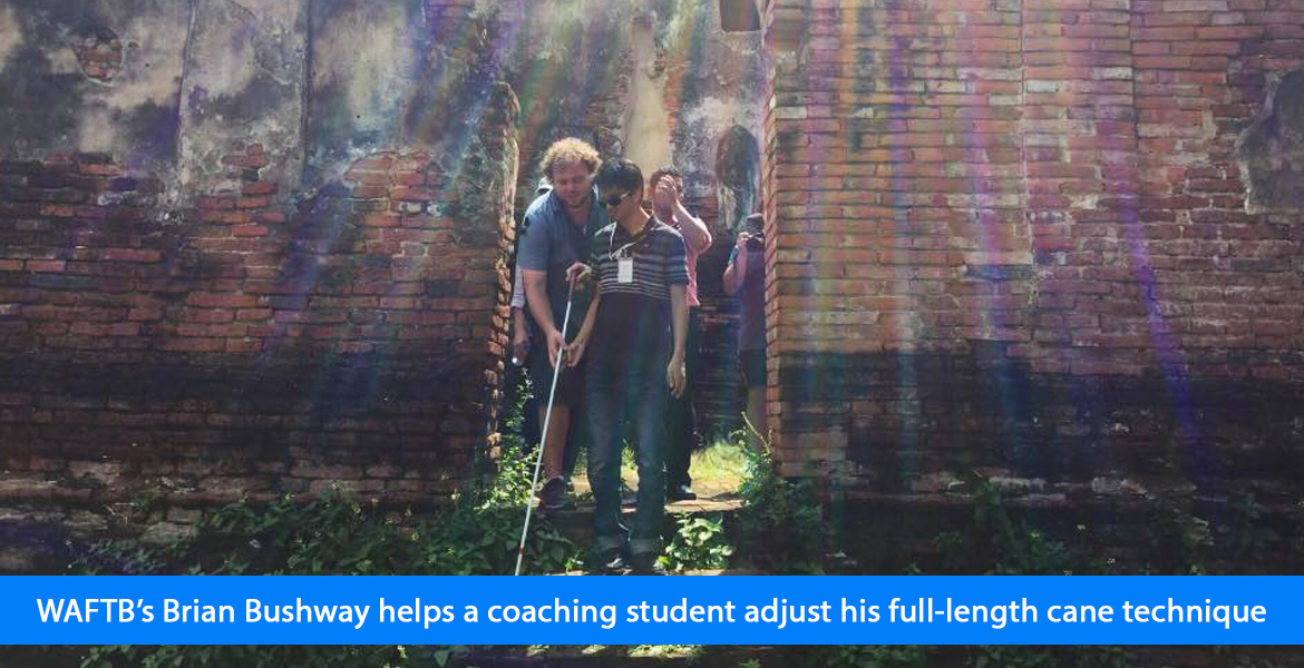 WAFTB's Brian Bushway helps a coaching student adjust his full-length cane technique. Image. Photo shows rays from the sun streaming down as Brian Bushway and a student step down from a passageway between the ruins at Ayutthaya Historical Park in Thailand.
