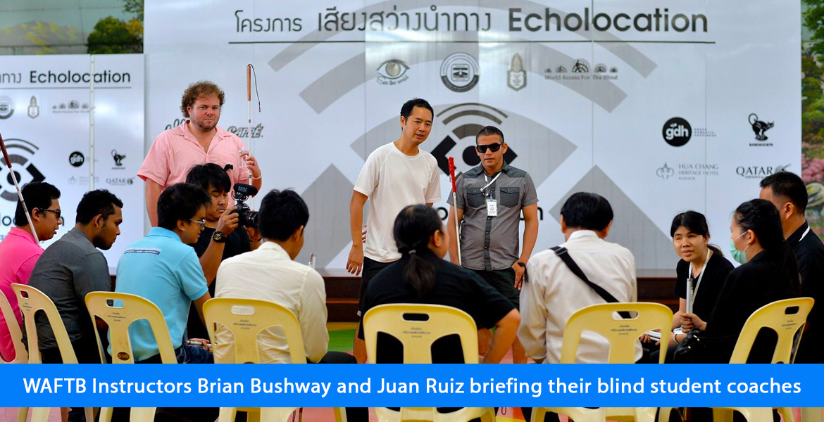 WAFTB Instructors briand Bushway and Juan Ruiz briefing their blind student coaches. Image. The students are seated in a semi-circle of chairs as Brian and Juan brief them via an interpreter.