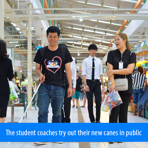 The student coaches try out their new canes in public. Image shows one of the students walking with his full-length cane.