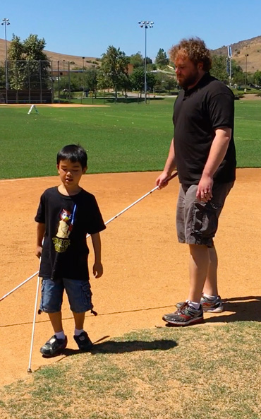 Photo shows WAFTB Perceptual Navigation Instructor Brian Bushway supervising as our student Nathan discovers the shape of a baseball diamond. using his full-length cane technique.