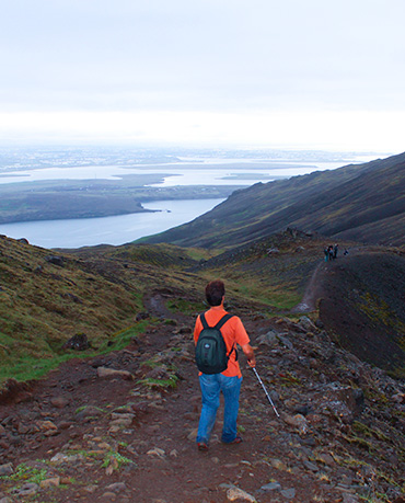 Photo: Daniel Kish is photographed from behind as he navigates down a mountain hiking path in Iceland.