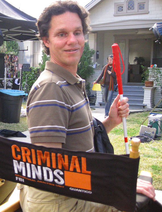Image: Photo shows Daniel Kish sitting in a 'Director's chair that has the logo of the TV show 'Criminal Minds' embroidered on the back while on location in front of a house where a scene is being filmed.