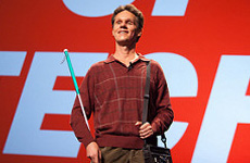 Image shows Lead Visioneer Daniel Kish gives an activational talk onstage with the PopTech logo behind him.